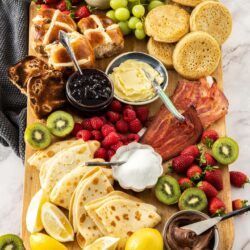 A wooden board filled with breakfast foods.