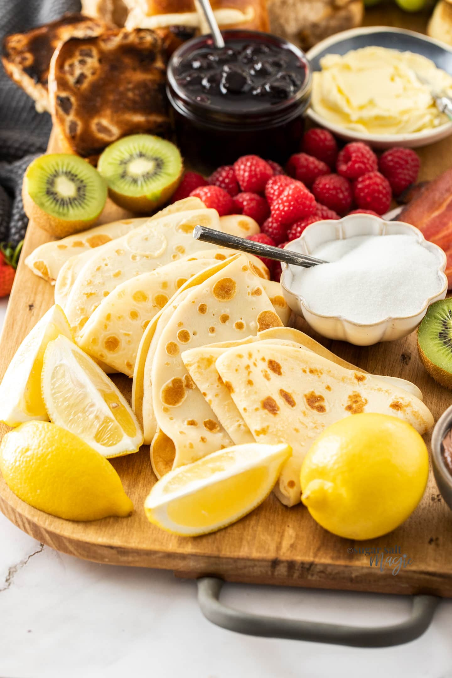 English pancakes with lemon and sugar on a breakfast platter.