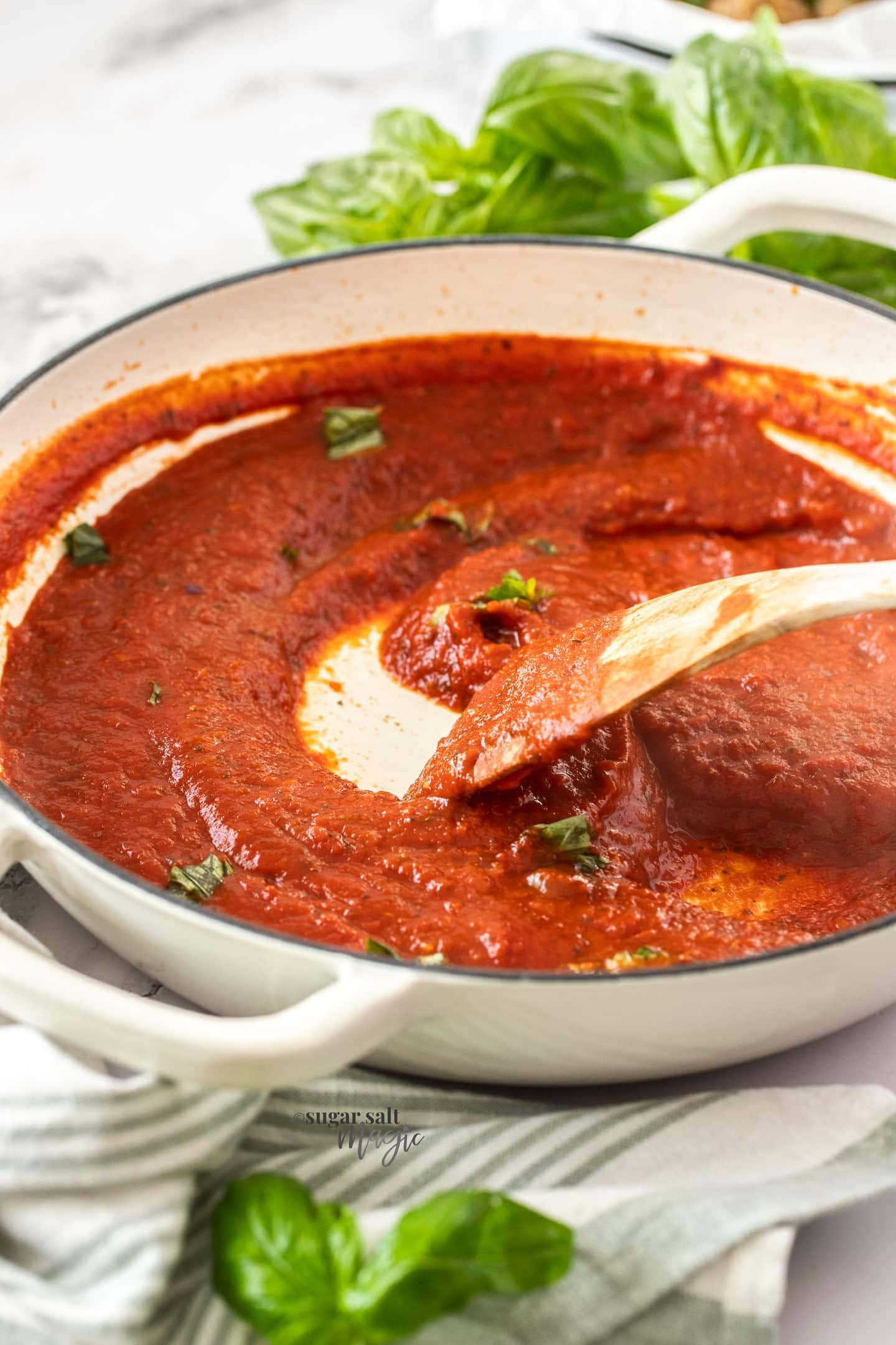 A white pan filled with tomato sauce.