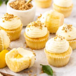 A batch of lemon cupcakes on a wooden board.