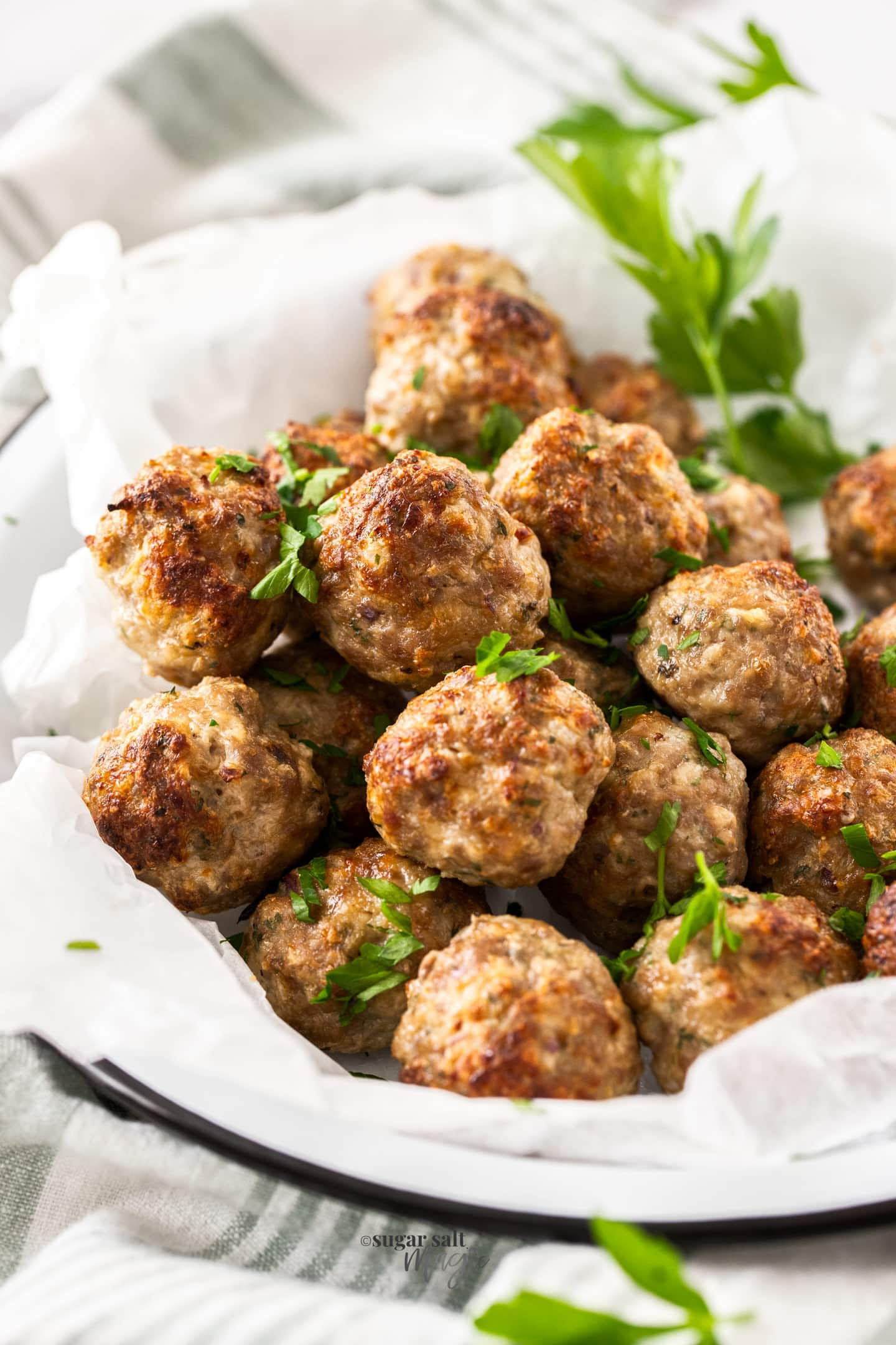 A white dish filled with meatballs.