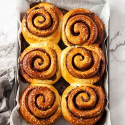 6 large cinnamon buns on a baking tray.