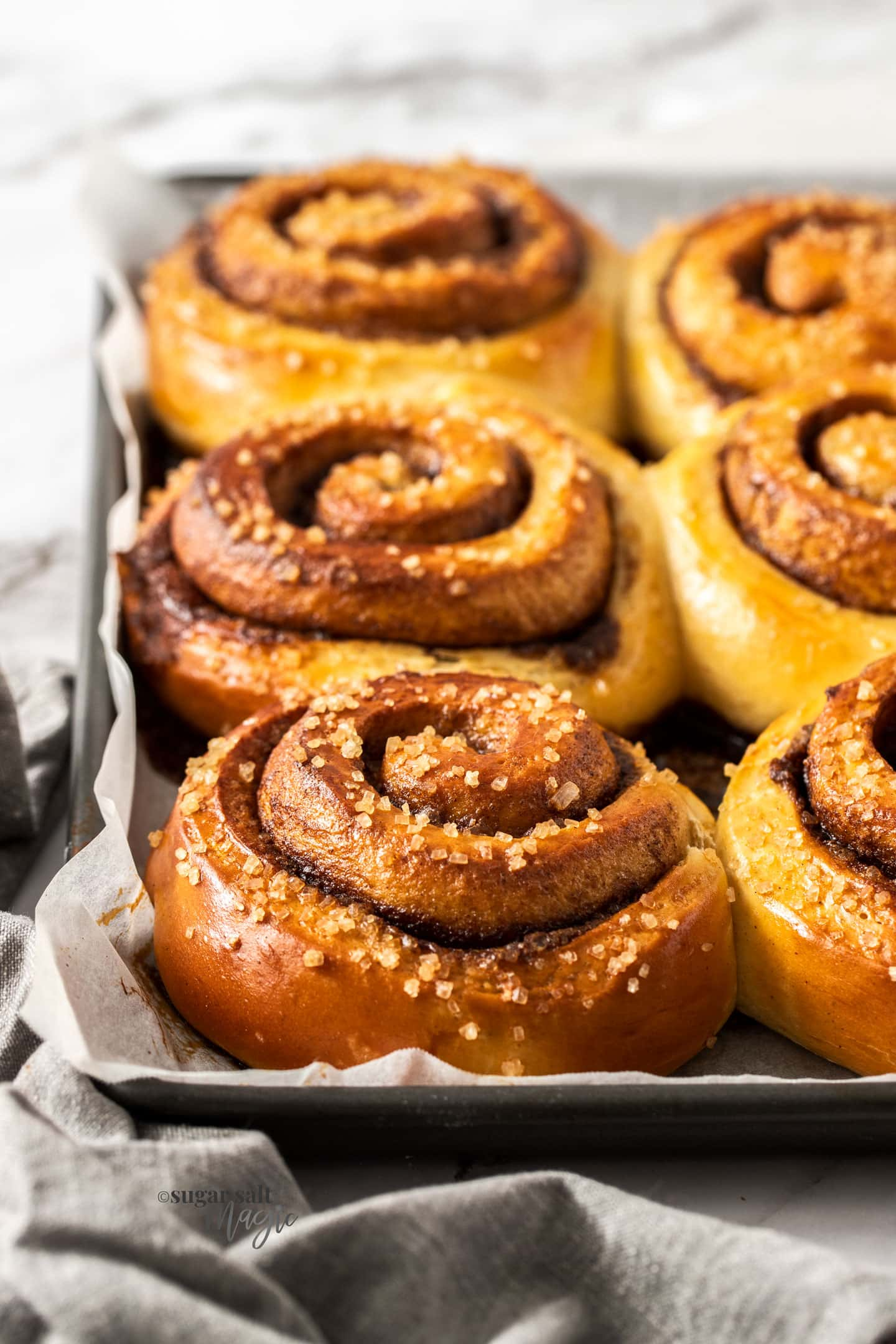 A row of 3 cinnamon buns on a baking tray.