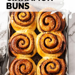 6 cinnamon buns on a baking tray.