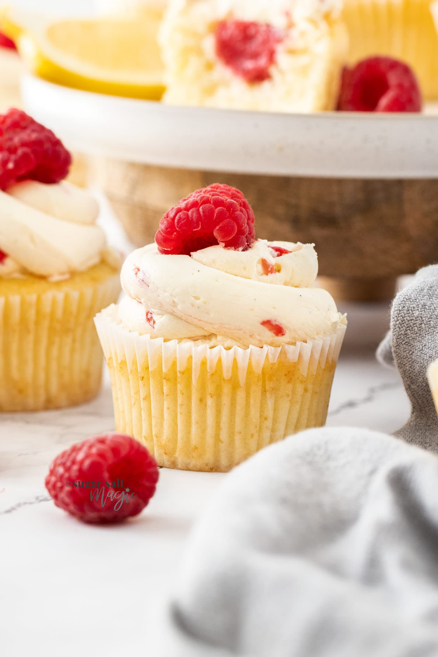 Closeup of a cupcake with a raspberry on top.