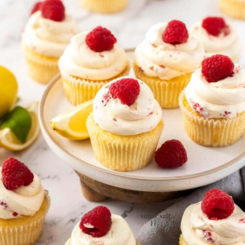 A batch of cupcakes topped with raspberries on a white plate.
