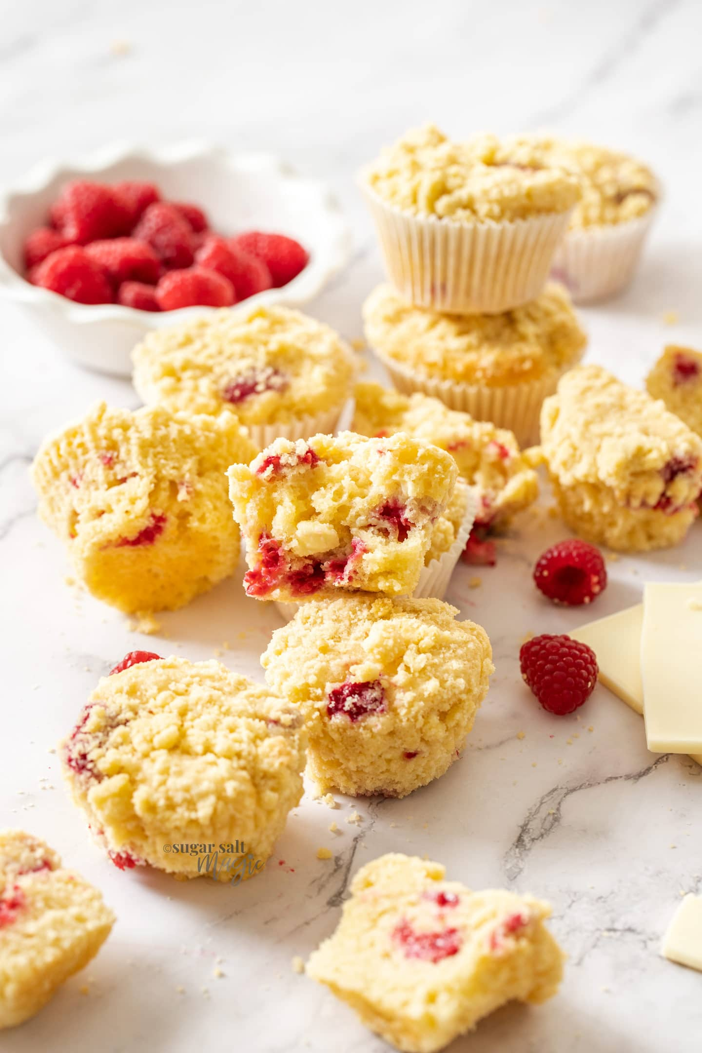 A batch of muffins with raspberries around them on a marble benchtop.