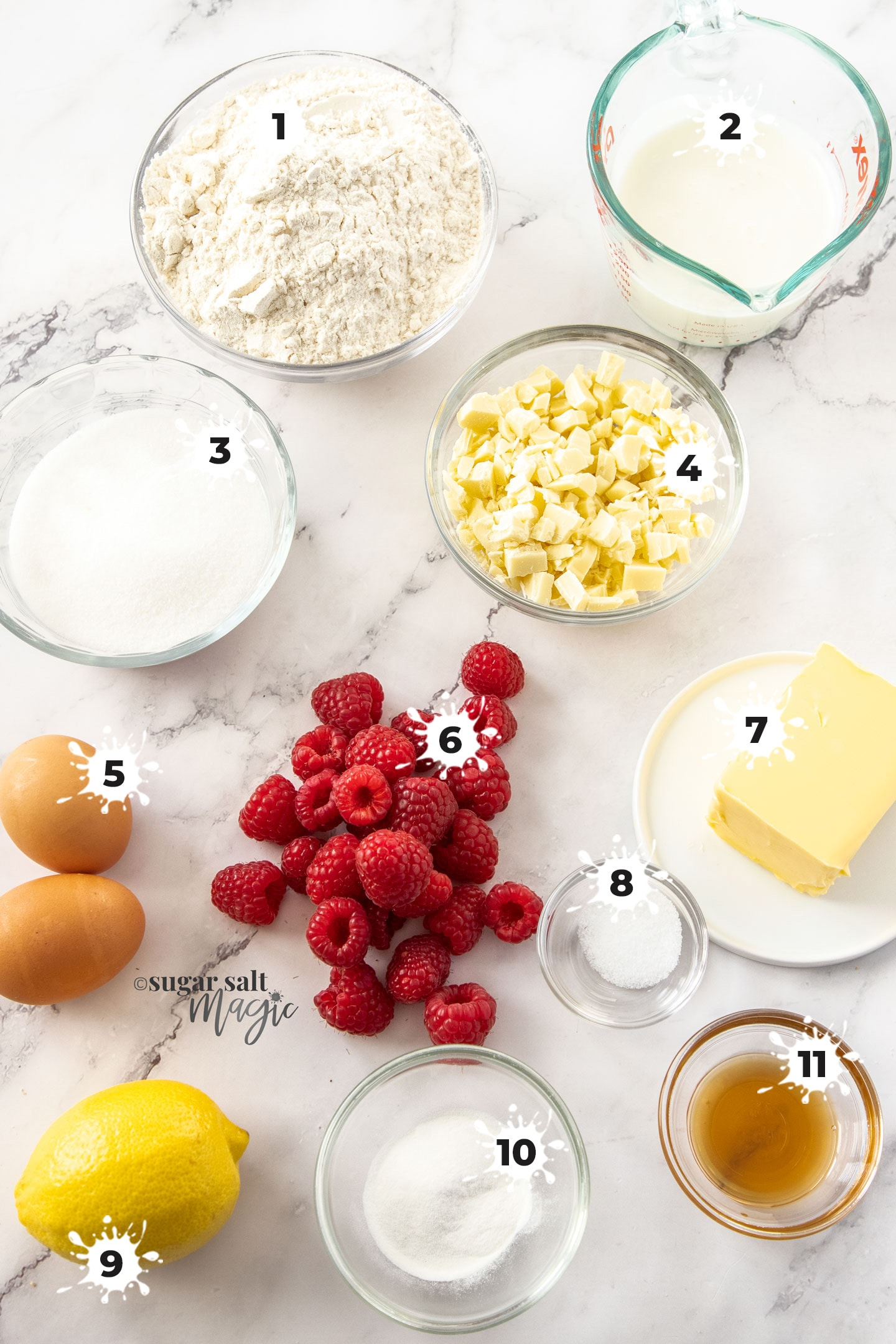 Ingredients for raspberry white chocolate muffins on a marble benchtop.