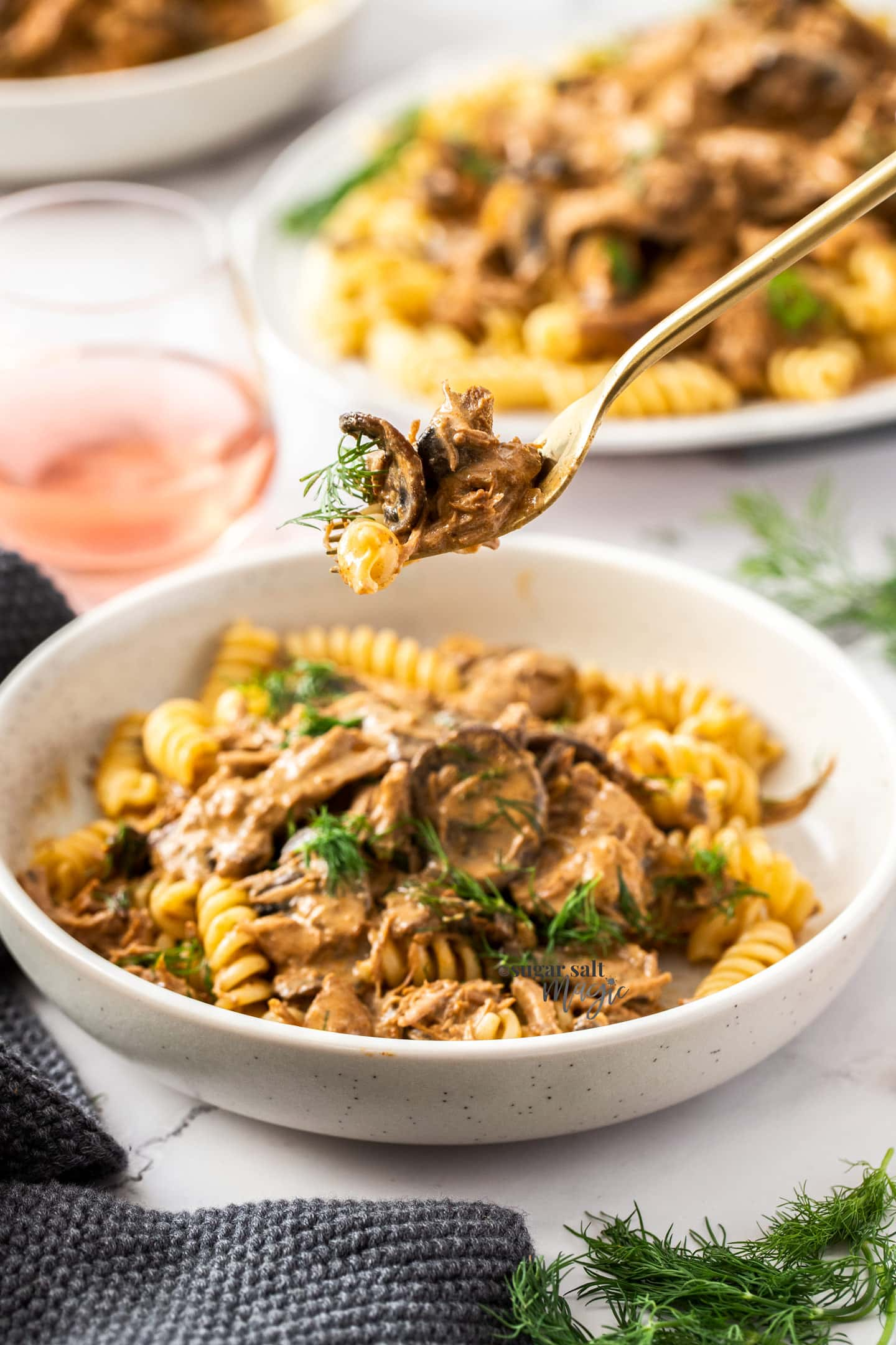A fork with meat and pasta being taken from a bowl.