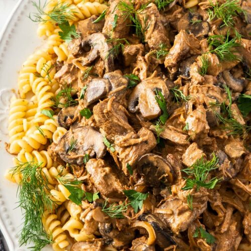 A white dish filled with pasta and beef stroganoff.