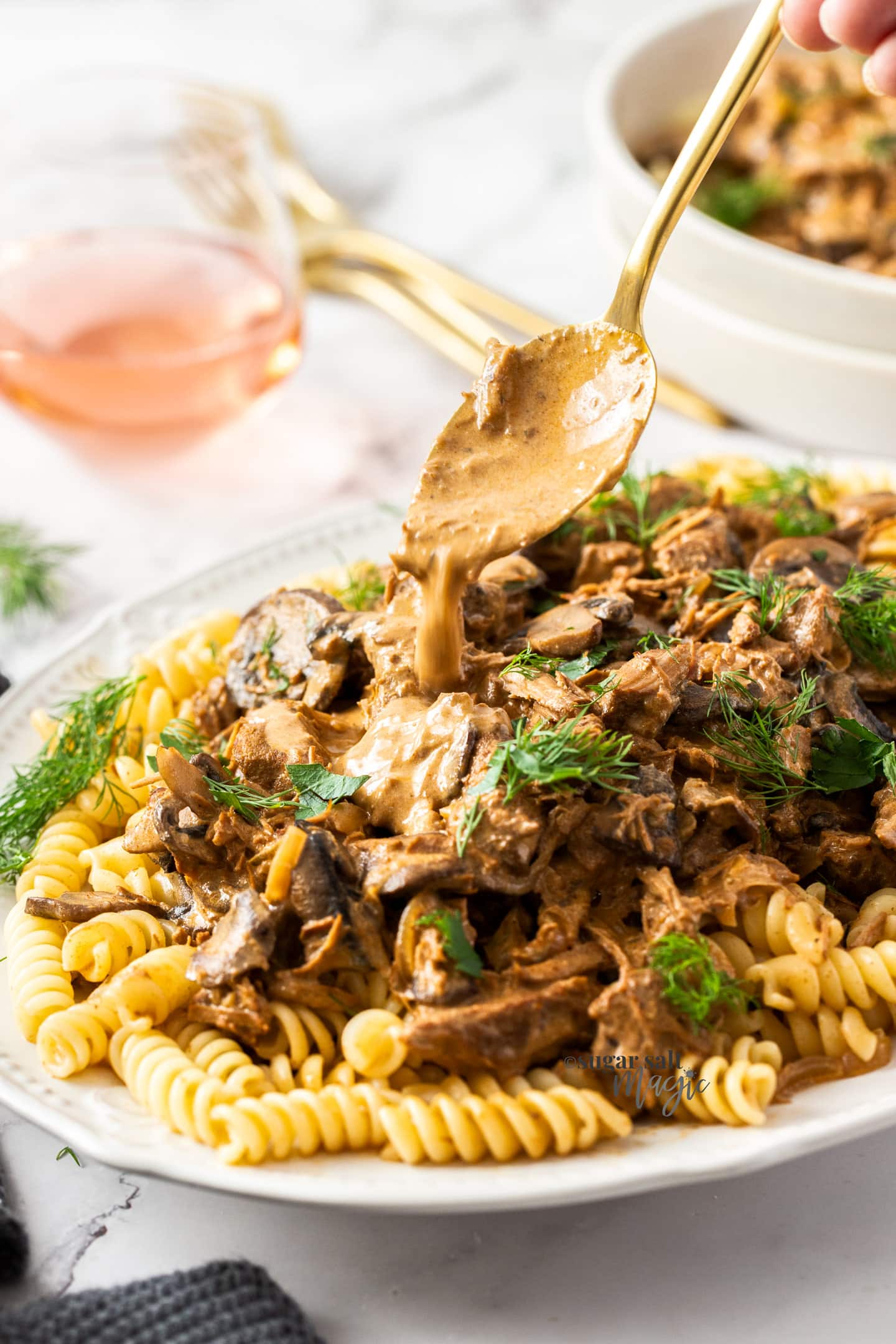 A spoon adding gravy to a white dish of beef and mushrooms.