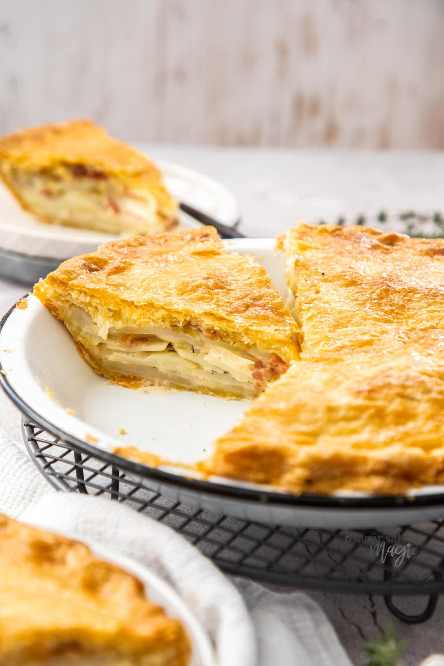 A potato pie in a pie tin with slices cut from it.