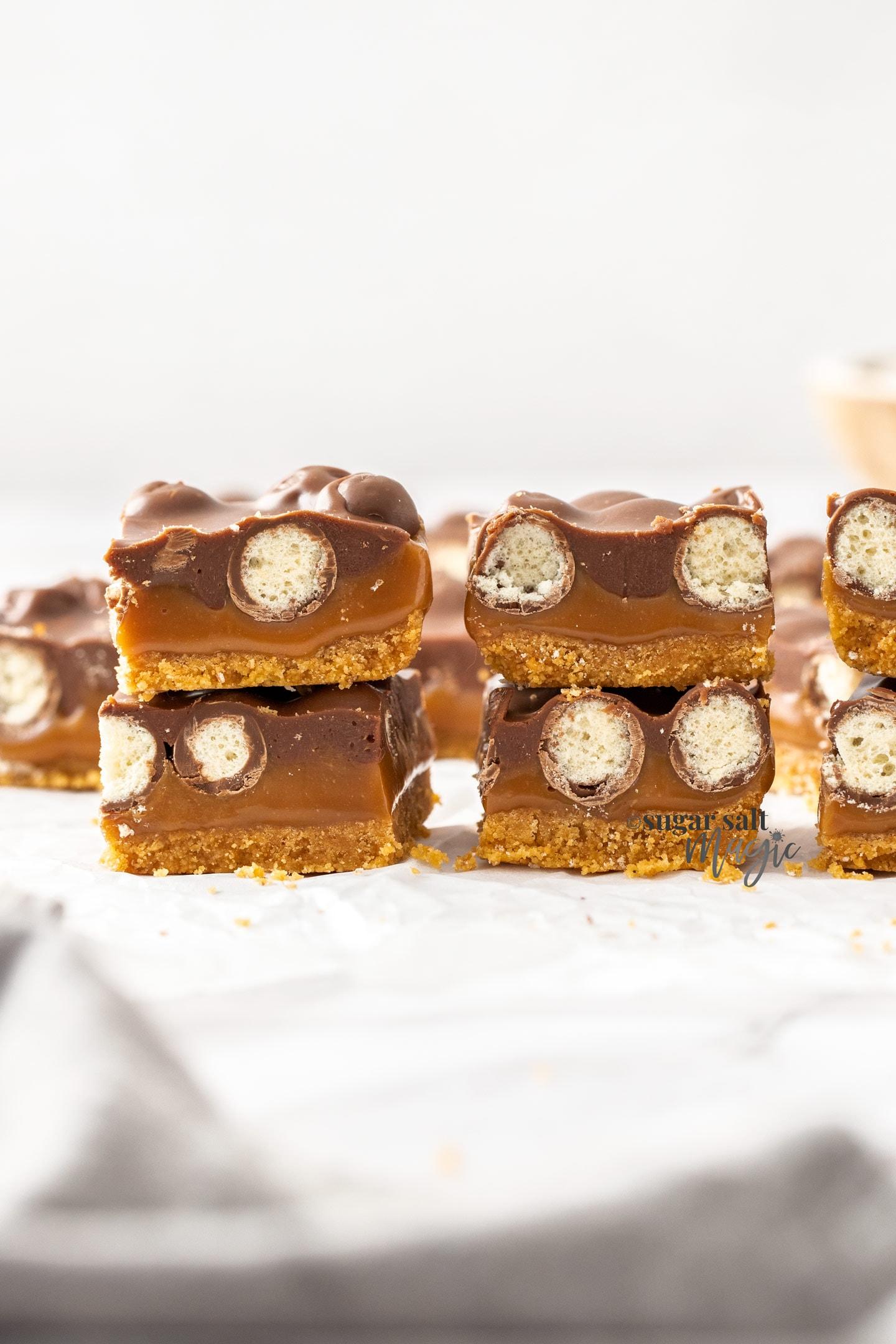 2 stacks of caramel malteser bars on a sheet of baking paper.