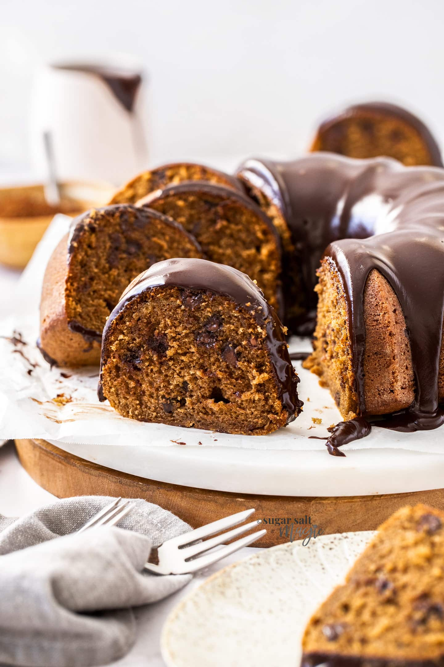 A bundt cake covered in chocolate ganache with slices sitting to the side.
