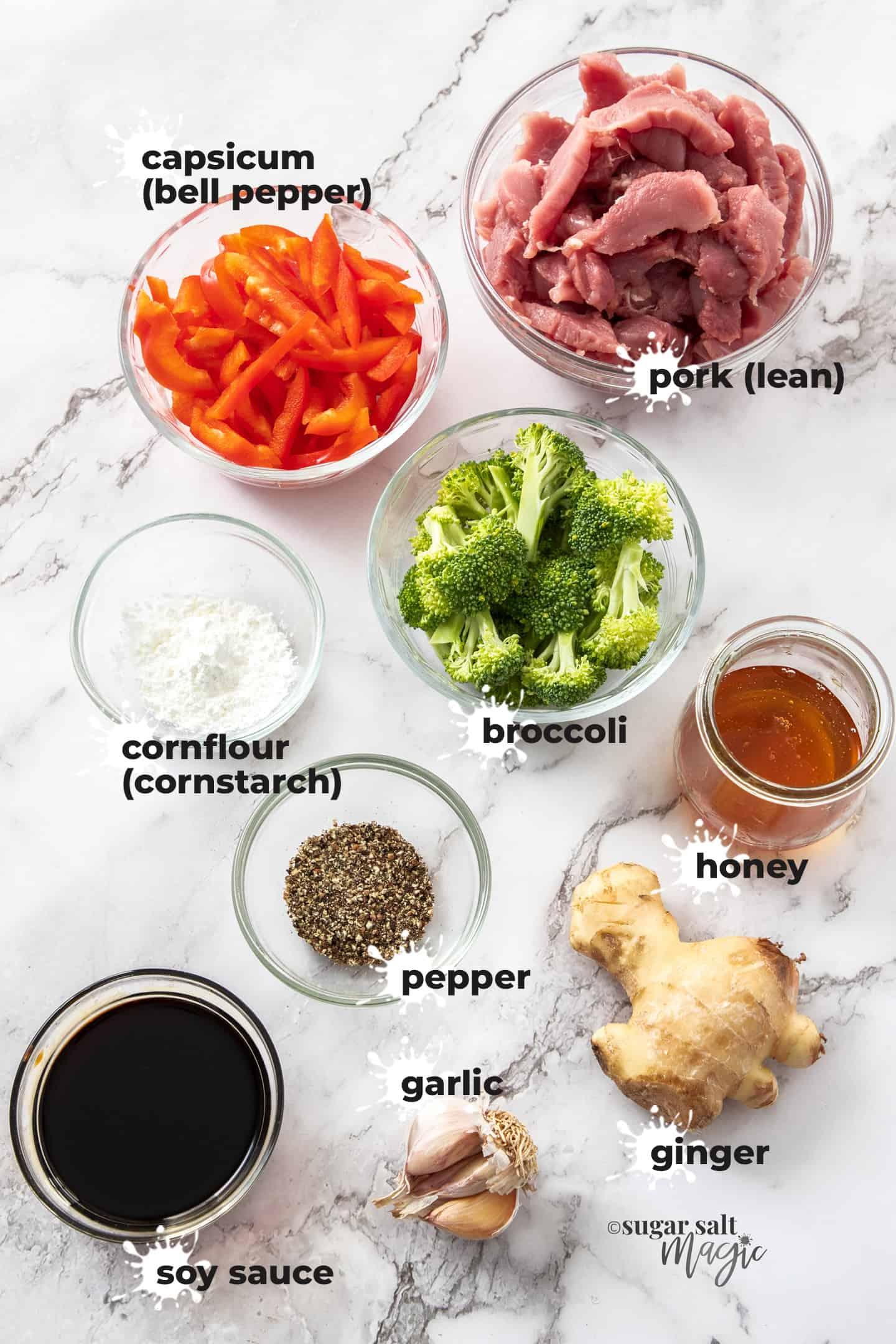 Ingredients for honey pepper pork stir fry on a marble background.