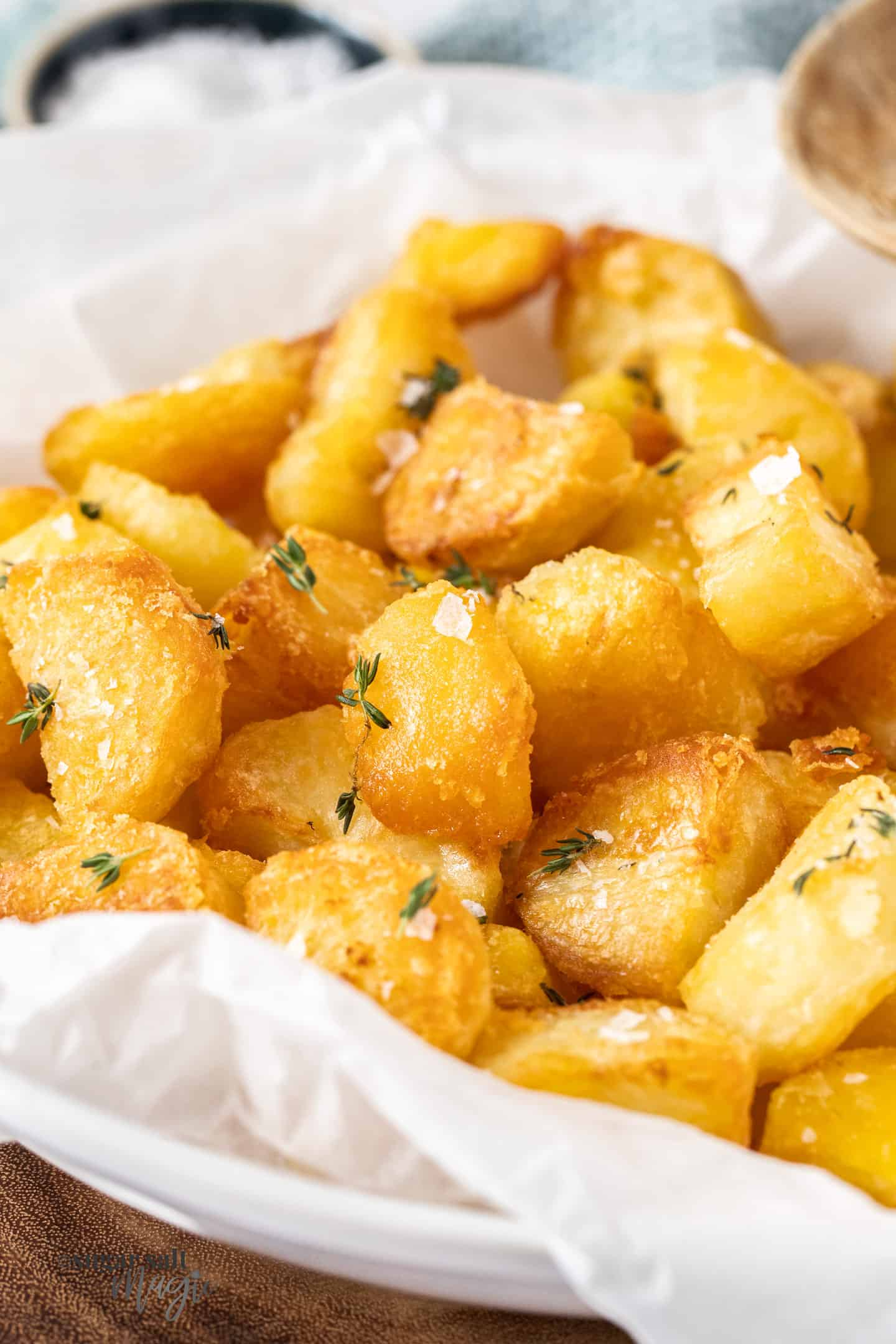 Crunchy roast potatoes with thyme and salt flakes in a white dish.
