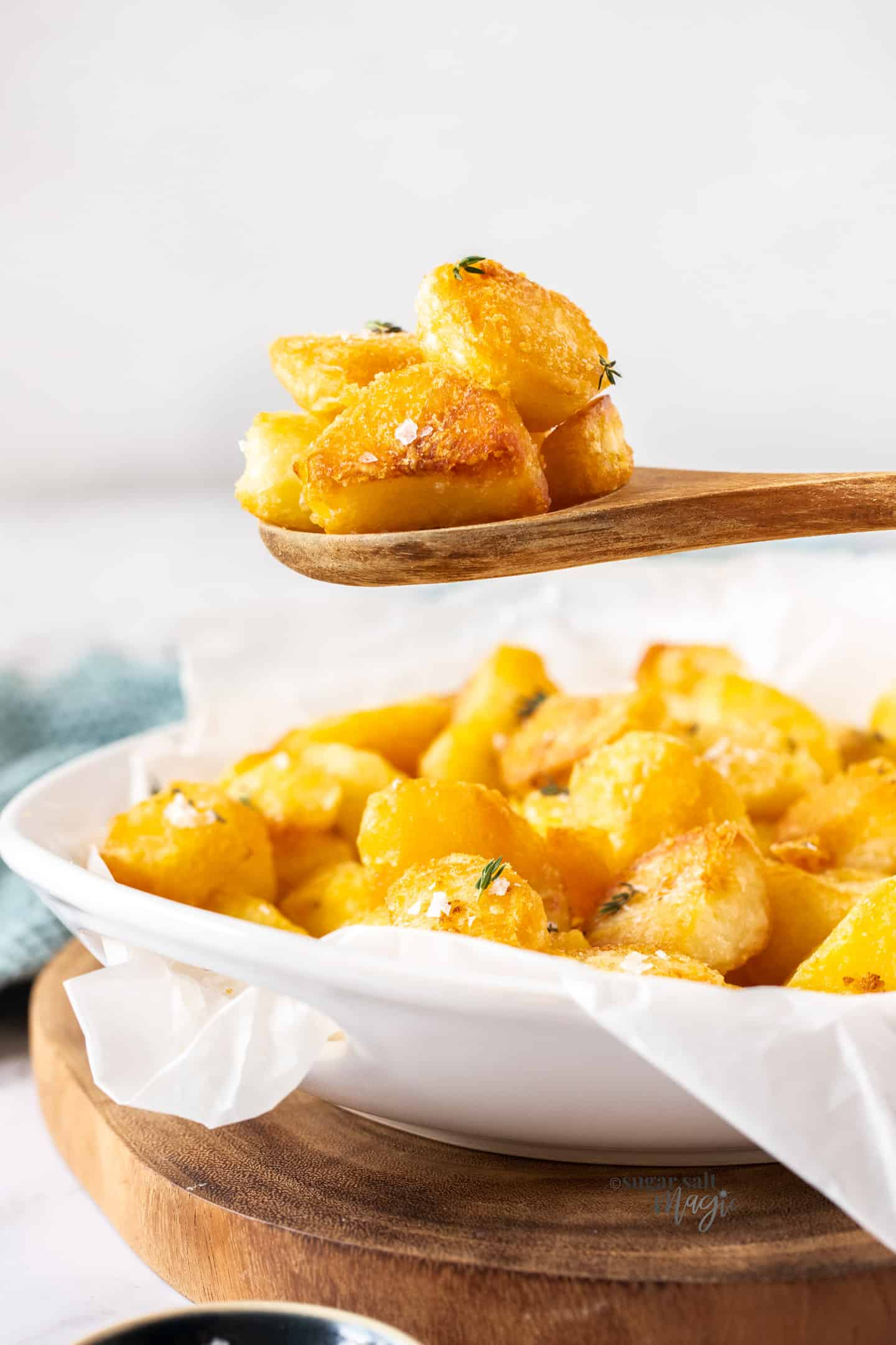 Roast potatoes on a wooden spoon held above a bowl of potatoes.