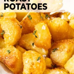Closeup of roast potatoes with thyme and salt flakes.