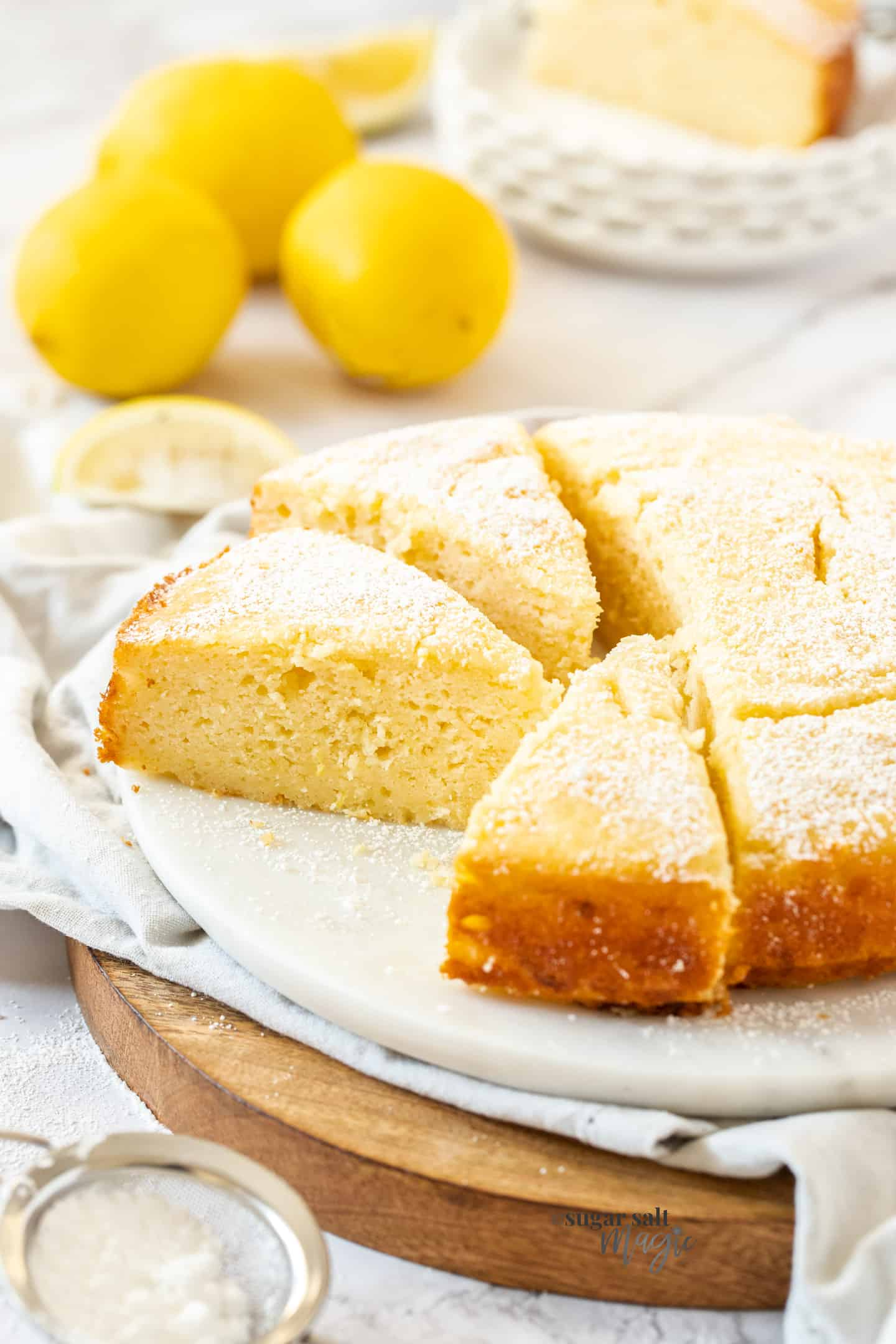 A lemon ricotta cake cut into slices on a white platter. Lemons in the background.
