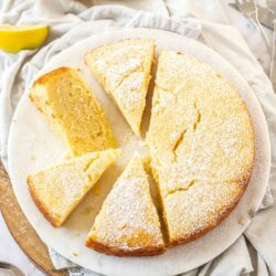 Top down view of a lemon ricotta cake cut into slices on a white platter.