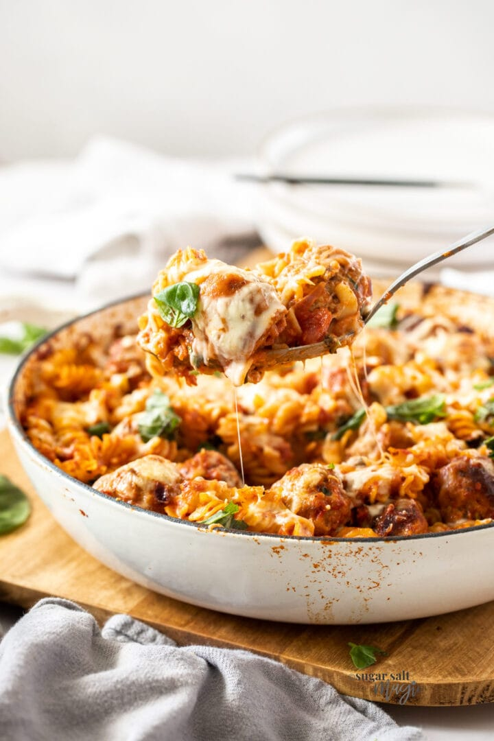 A spoon taking a scoop of pasta bake from a white casserole dish.