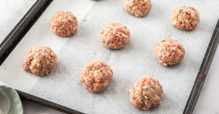A baking tray with 8 raw meatballs.