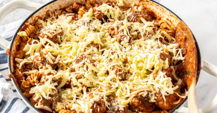 A white casserole dish filled with pasta bake, ready to bake.