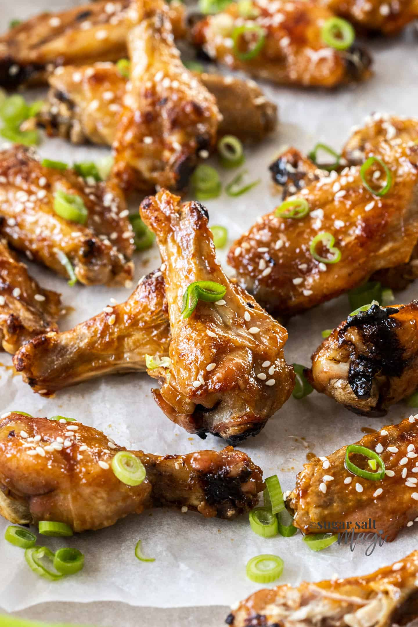 A batch of honey soy coated chicken wings on a sheet of baking paper.