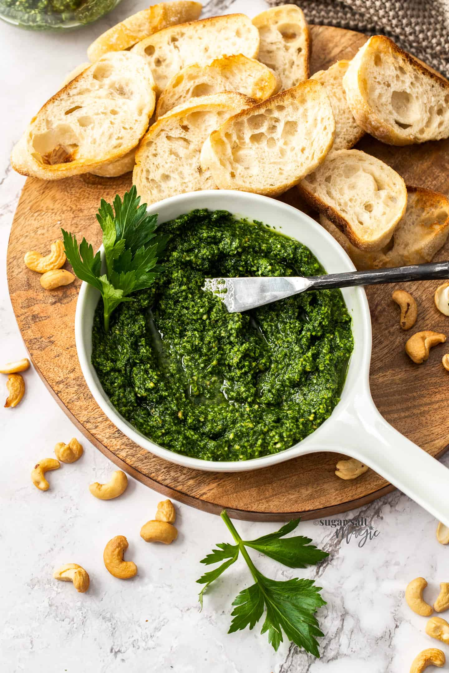 A white bowl filled with green pesto on a wooden board with slices of bread.
