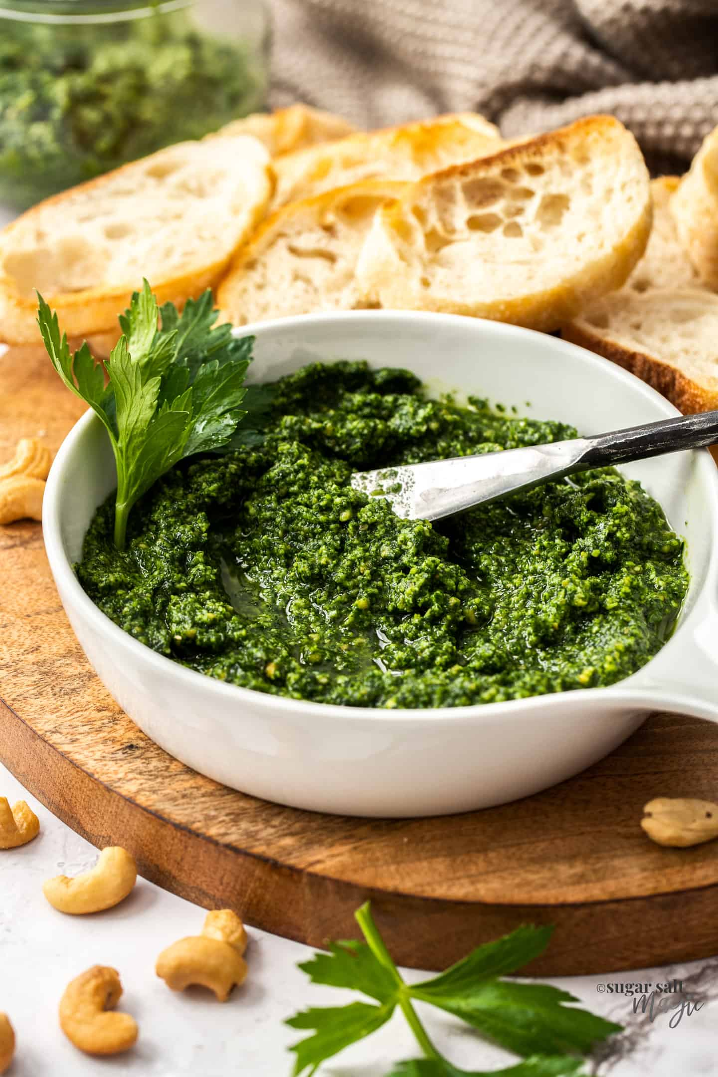 A white bowl filled with green pesto on a wooden board.