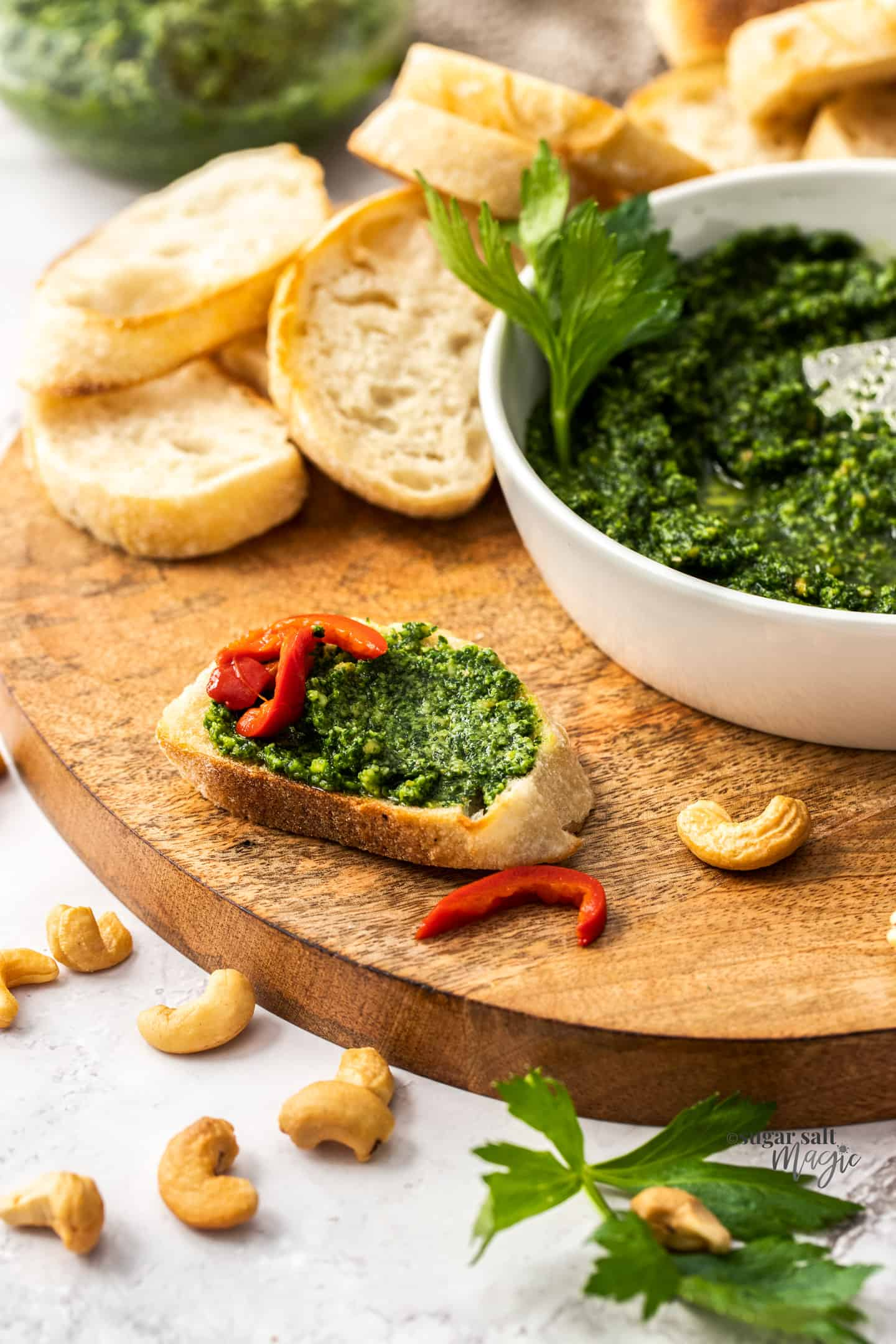 A small slice of baguette spread with celery leaf pesto.