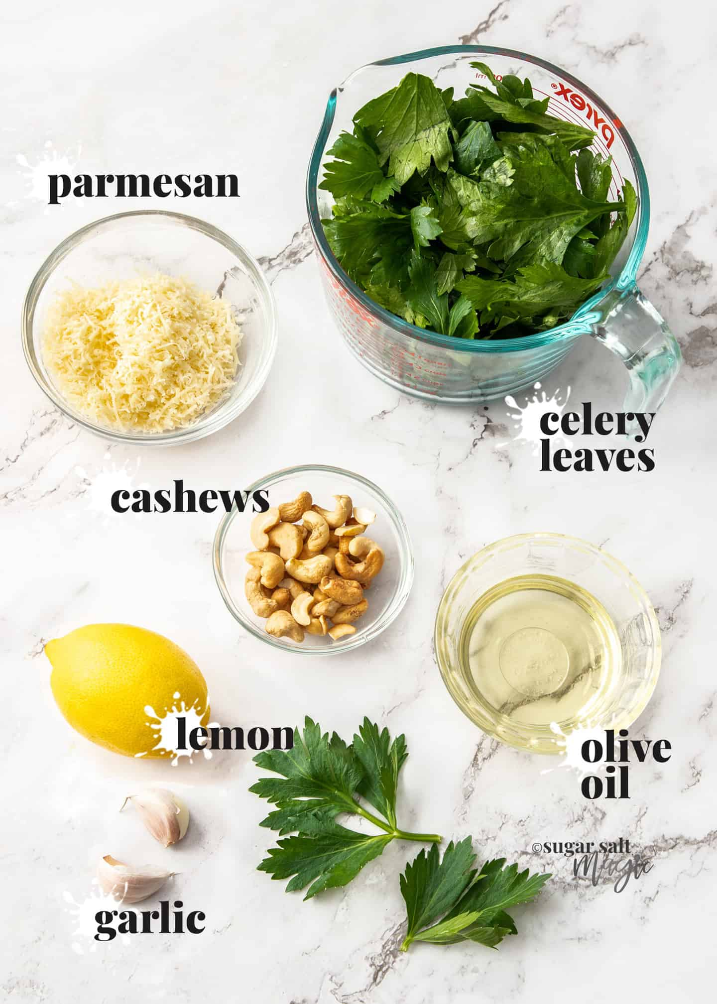 Ingredients required for celery leaf pesto on a marble surface.