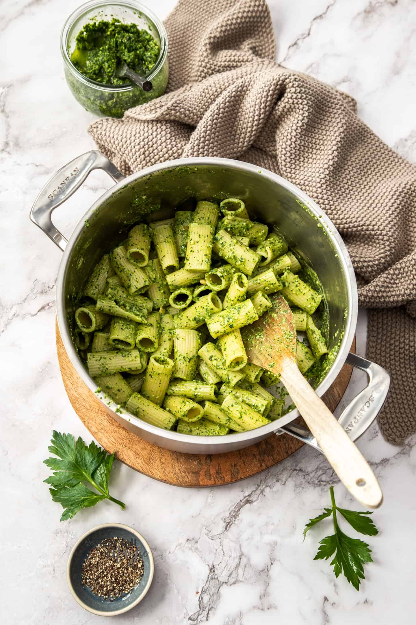 A saucepan filled with pesto covered pasta.