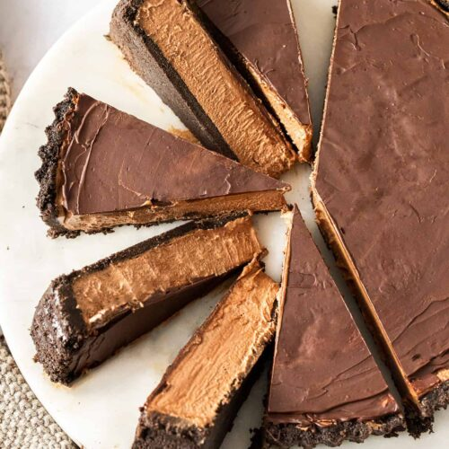 A sliced up chocolate tart on a white marble platter.
