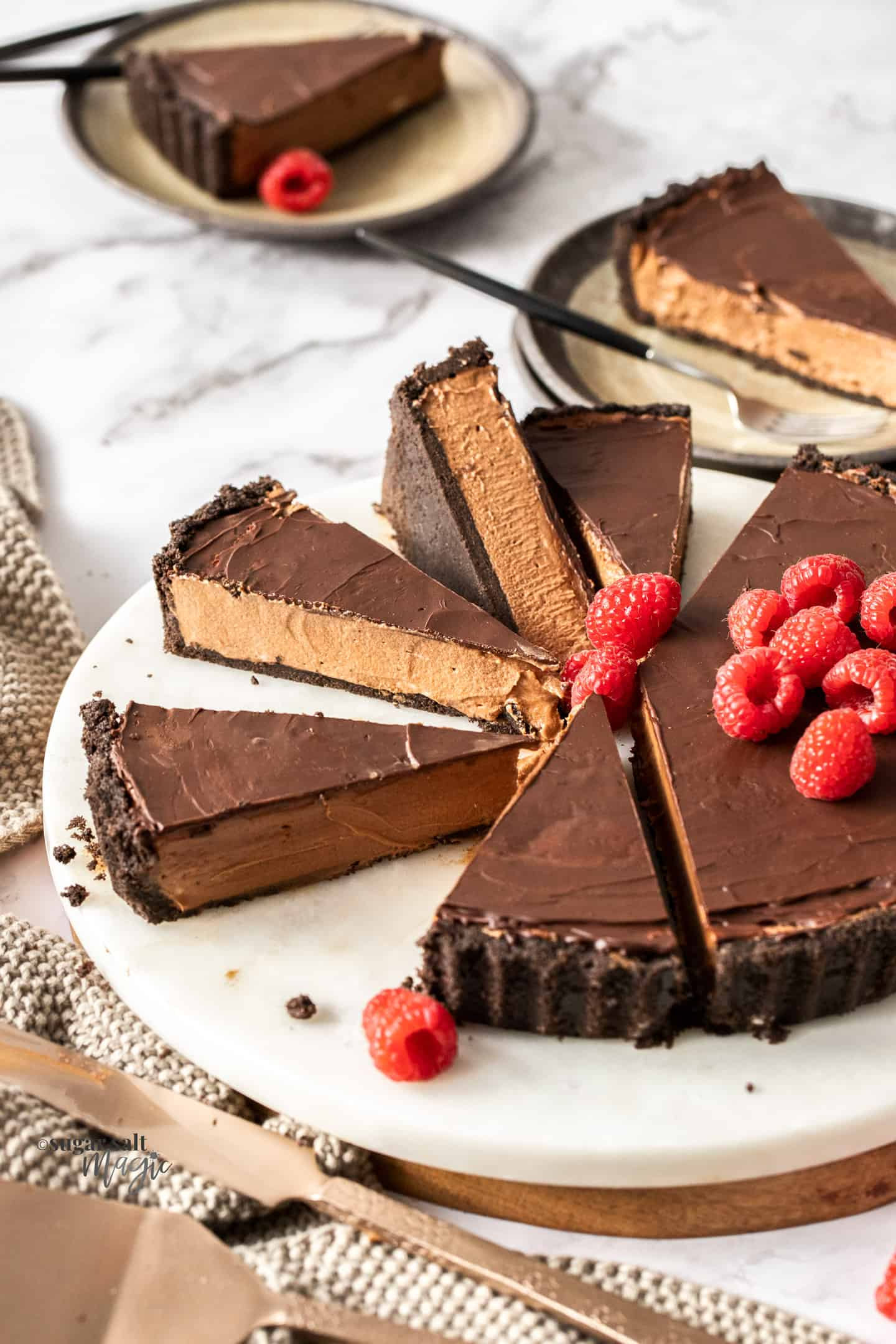 A sliced up chocolate tart topped with raspberries on a white marble platter.