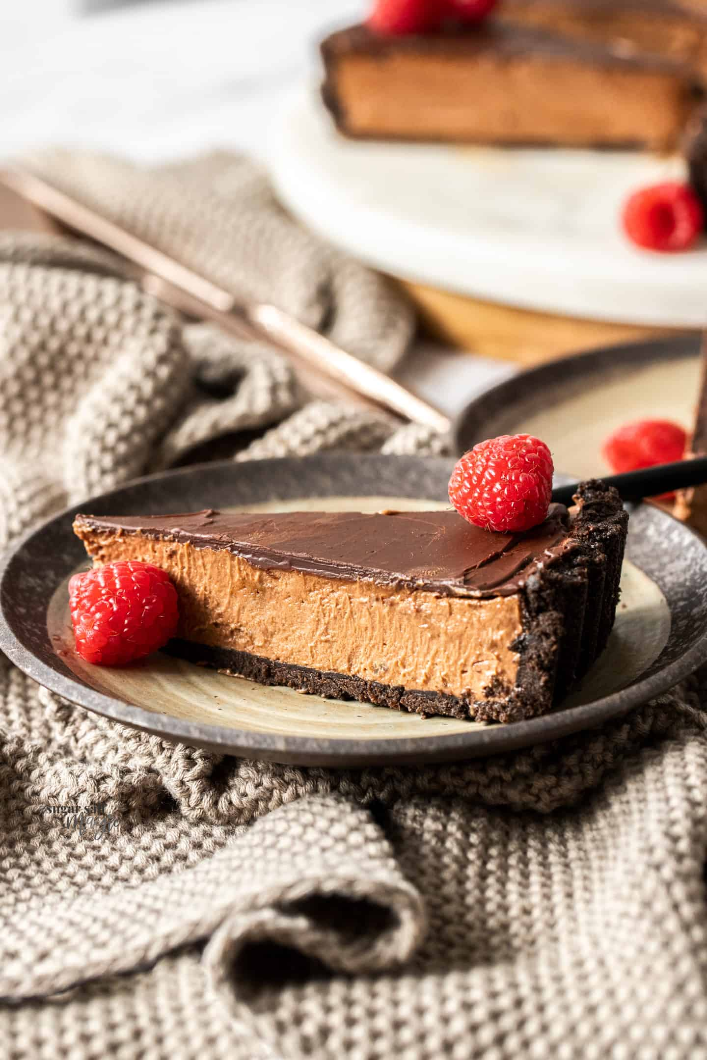 A slice of chocolate mousse tart on a brown cake plate with a crocheted napkin.