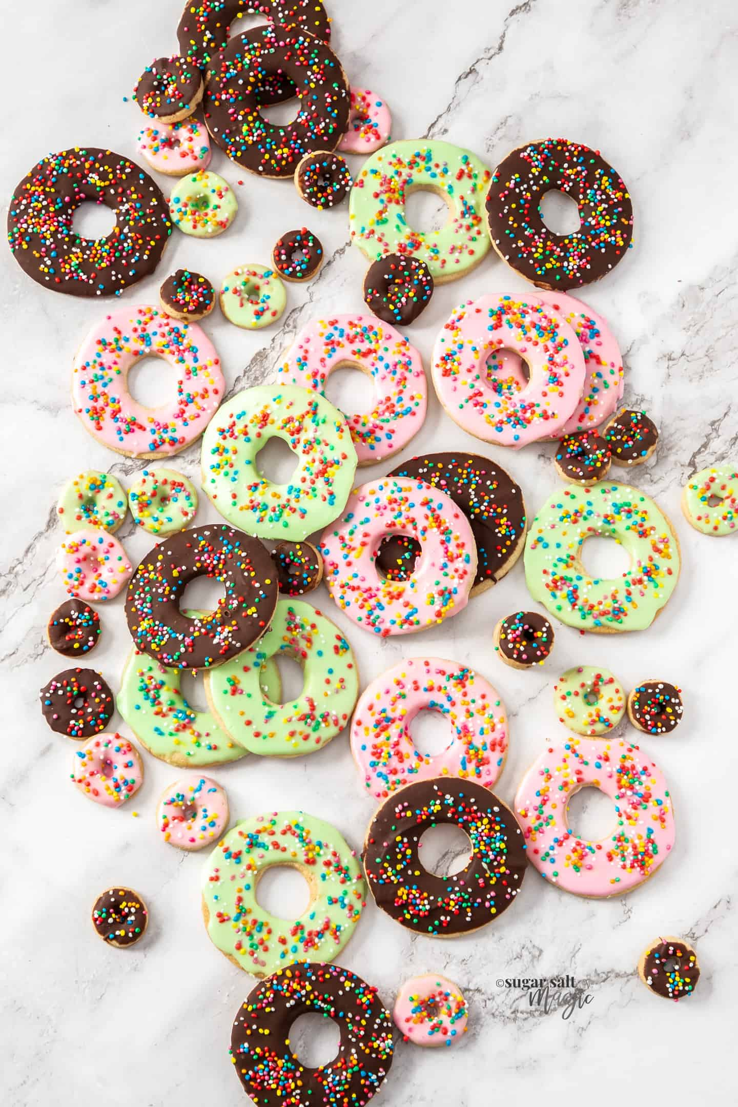 A batch of donut sugar cookies on a marble surface.