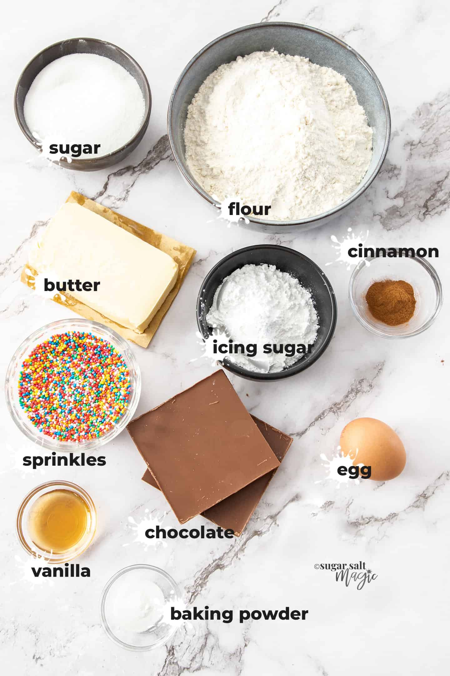Ingredients for donut cookies in bowls on a white marble benchtop.
