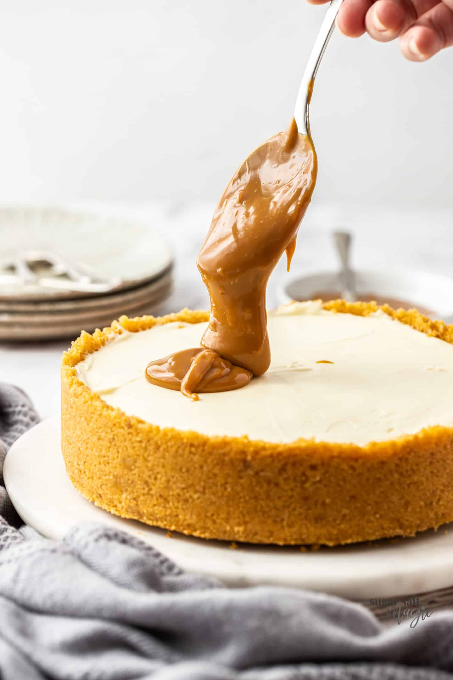 A big spoonful of dulce de leche being dropped onto the top of a cheesecake.