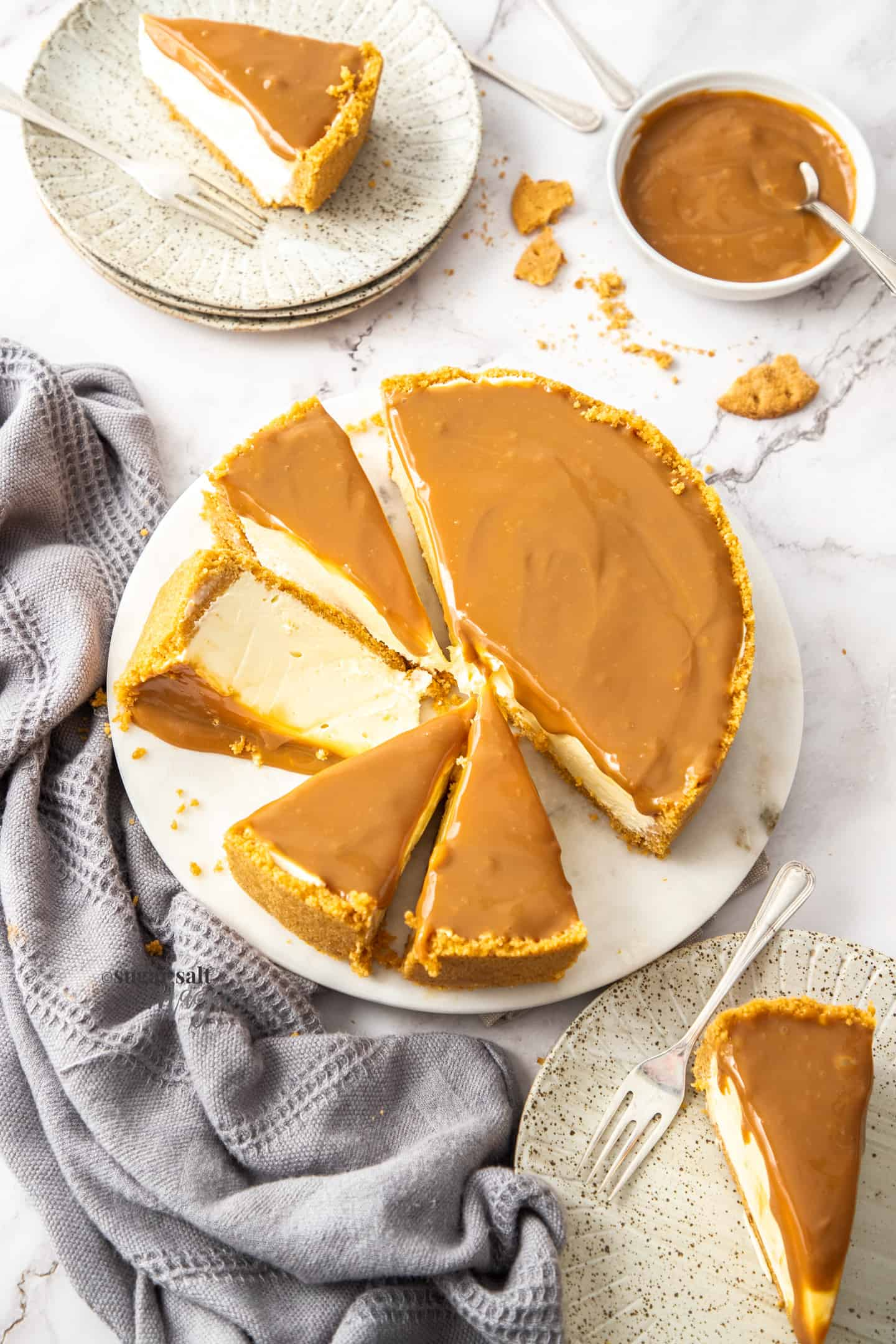Top down view of a cheesecake topped with dulce de leche cut into slices.
