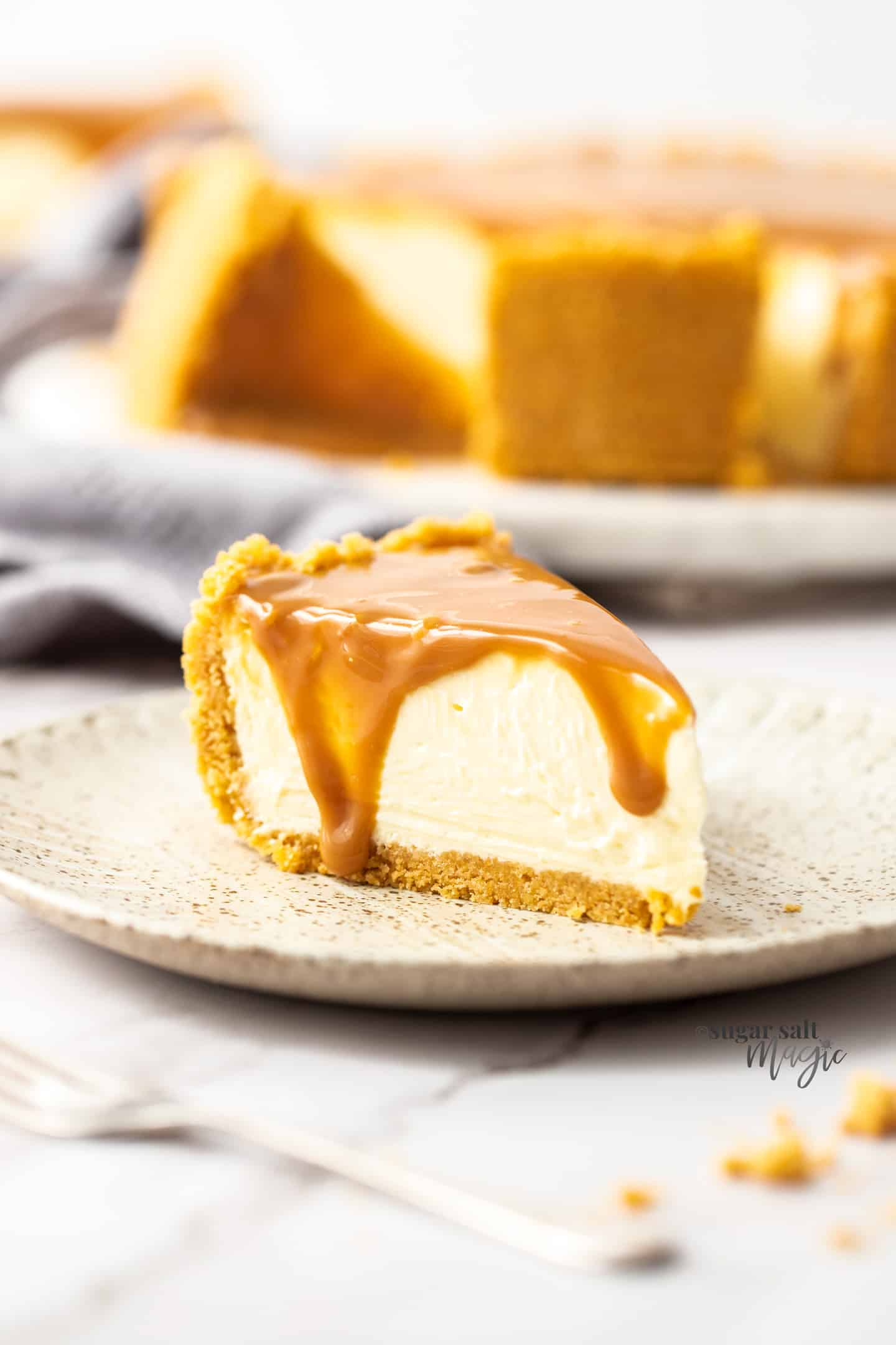 A slice of cheesecake with dulce de leche drippig down the side on a small plate.