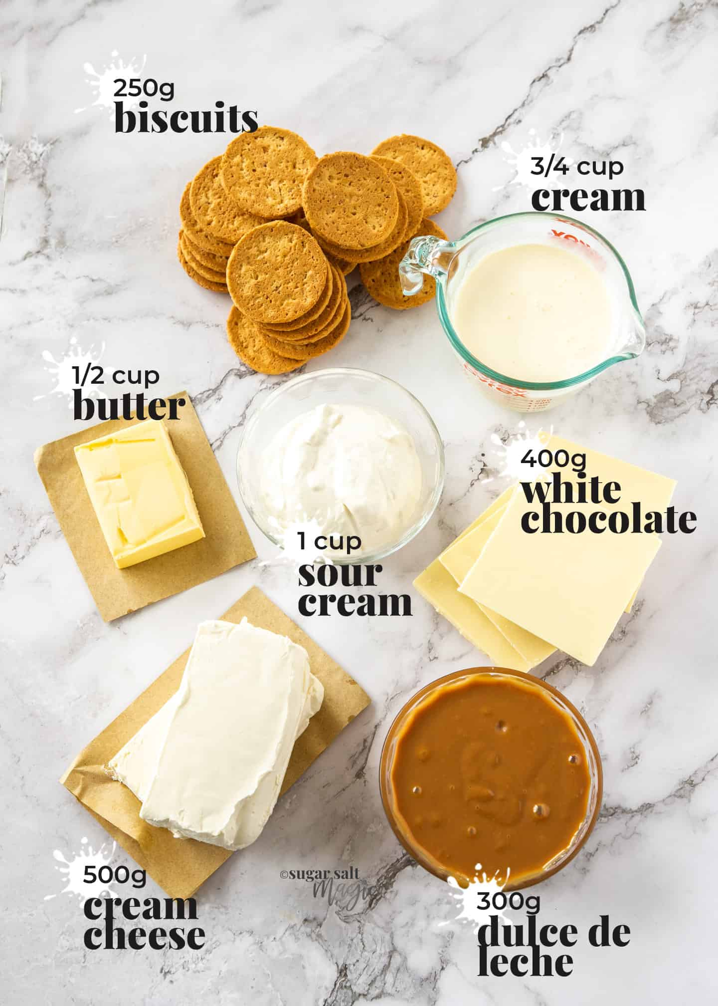 Ingredients for white chocolate cheesecake laid out on a marble benchtop.