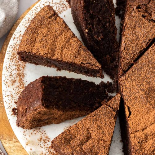 Closeup of a chocolate cake cut into slices on a white platter.