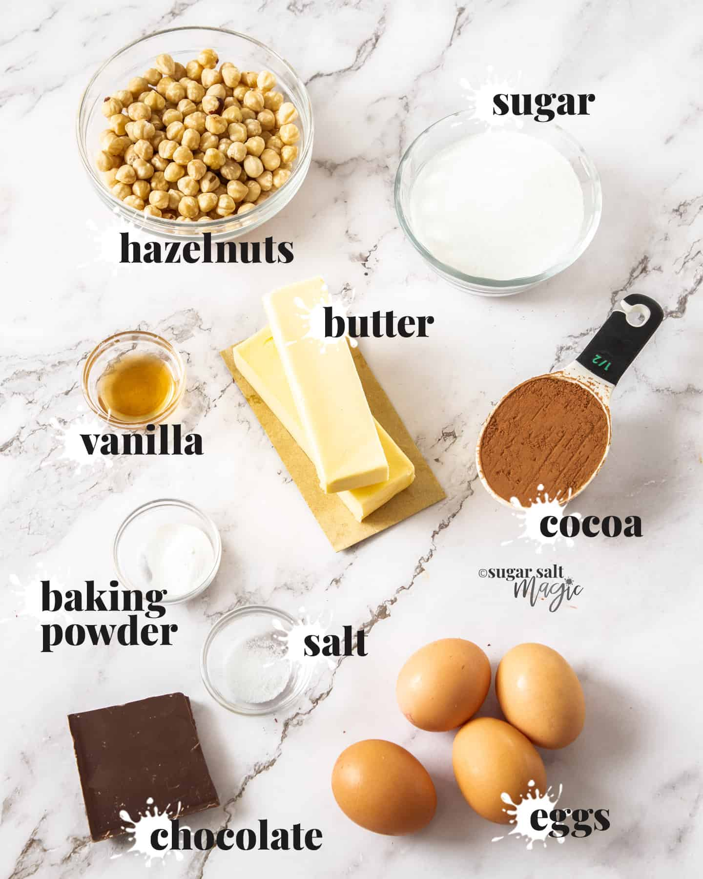 Ingredients for chocolate flourless cake on a white marble background.