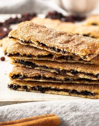 Closeup of a stack of 5 rectangular biscuits filled with fruit. Cinnamon stick in front.