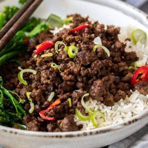 Closeup of a grey bowl filled with rice and crispy stir fried beef mince.