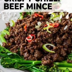 A white plate topped with broccolini and cooked crispy beef mince.