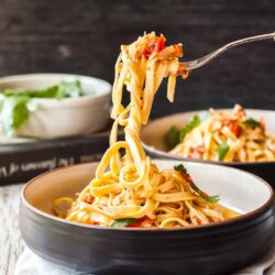 A fork lifting linguine out of a black bowl.