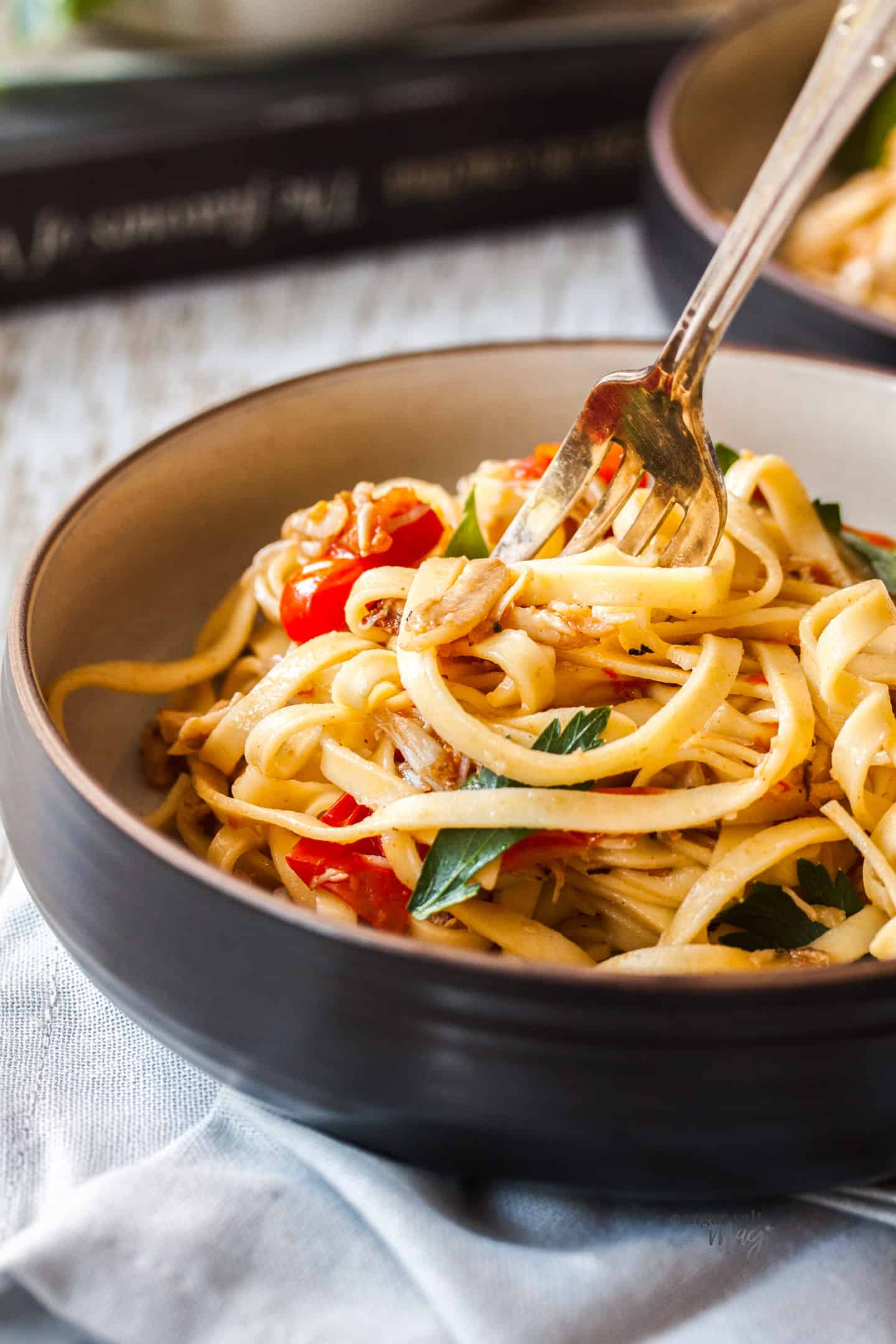 A fork digging into a bowl of linquine with crab and tomatoes in it.