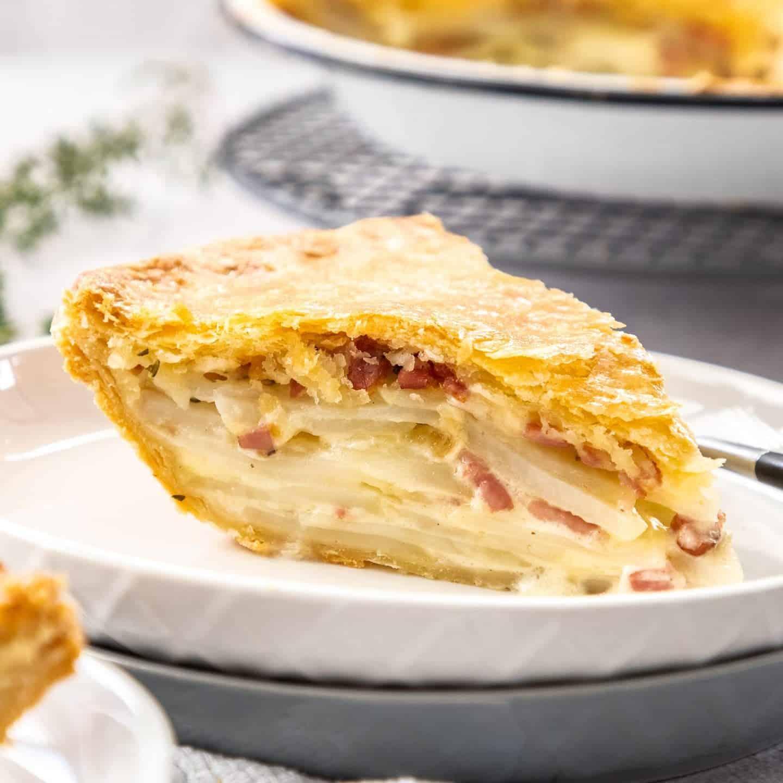A tall slice of potato pie on a white plate.